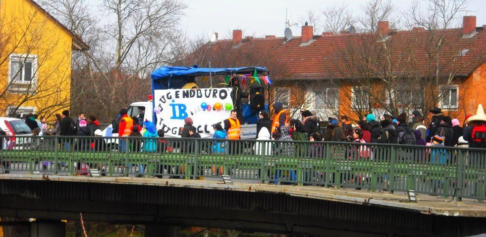 Menschen an Fasching laufen über die Omega-Brücke in Griesheim